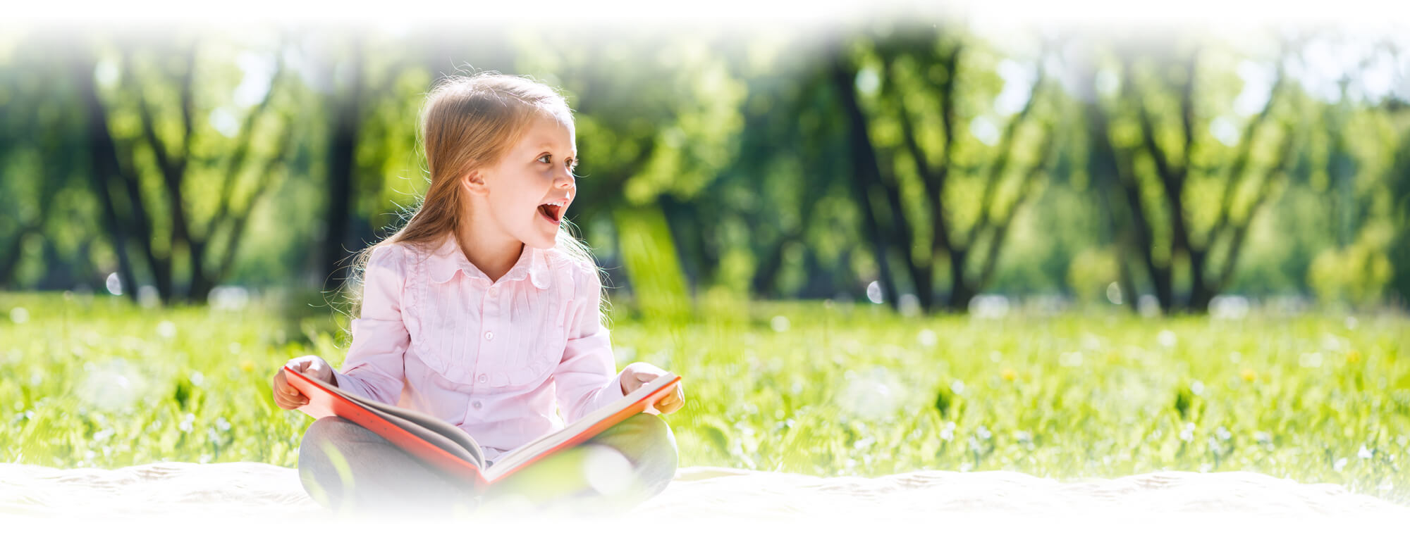 excited young girl holding book