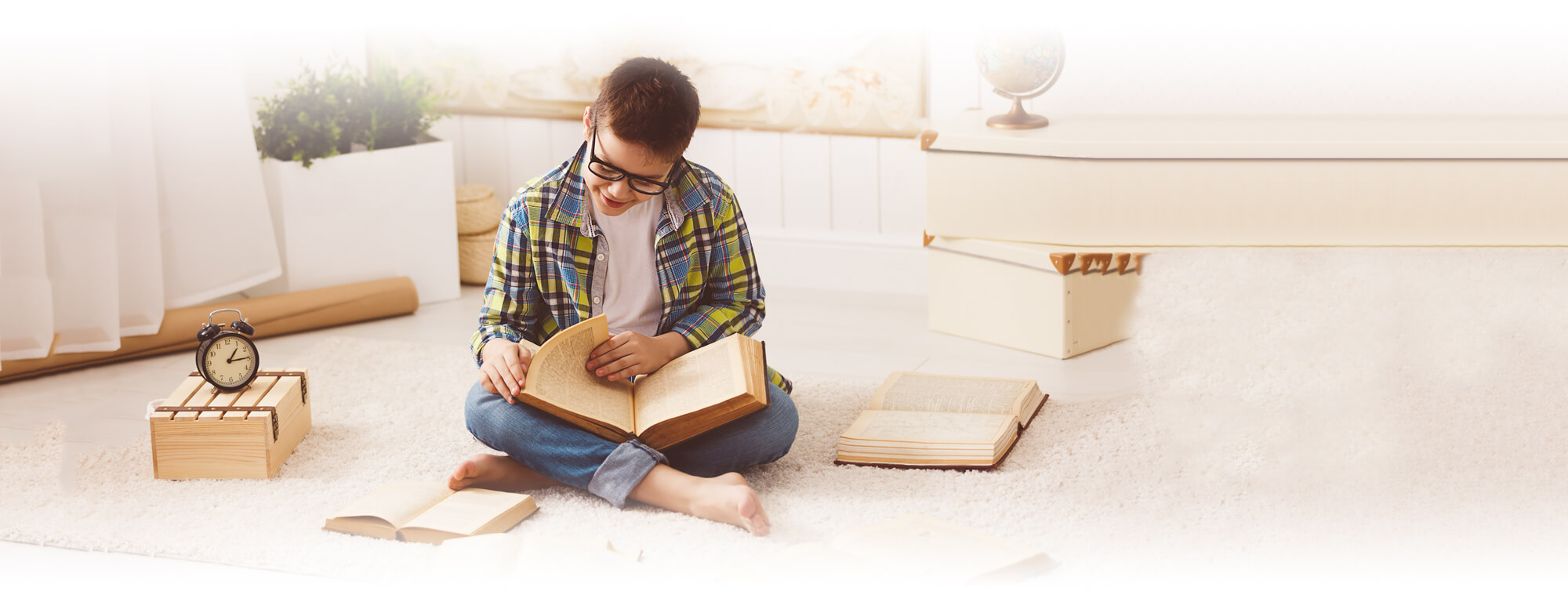 student boy sitting on floor reading book
