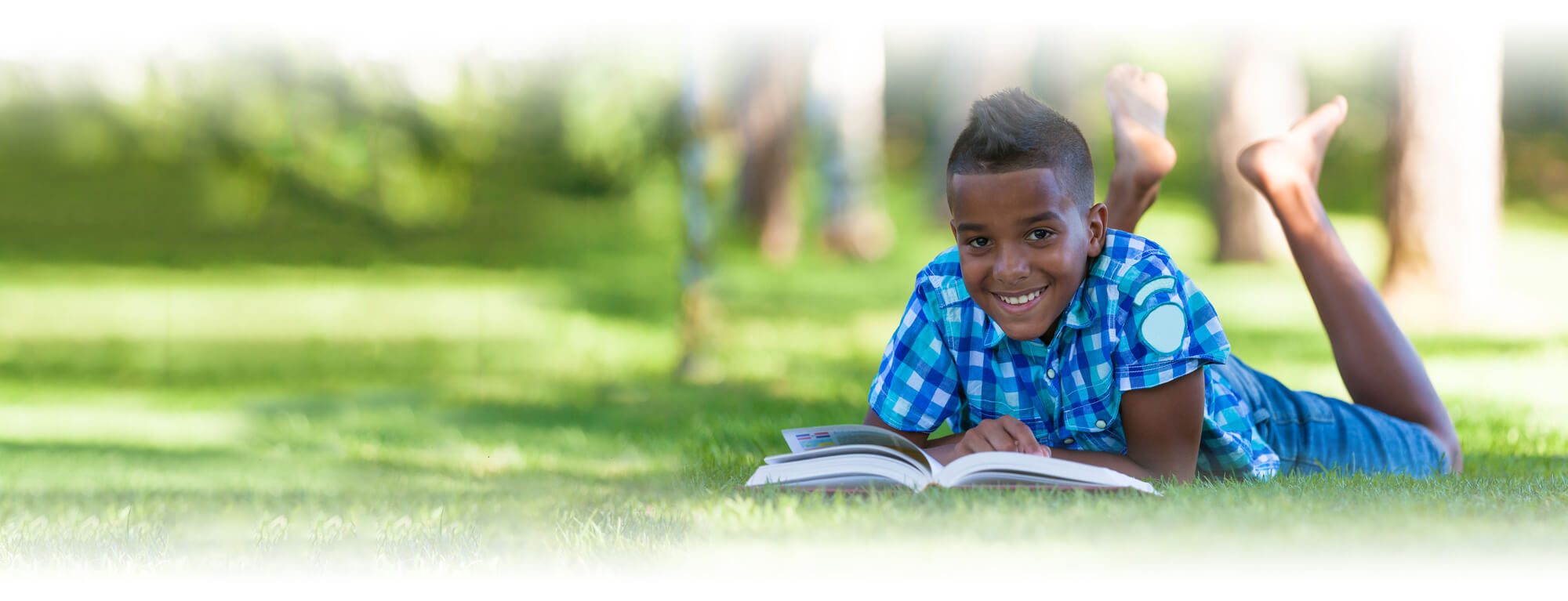 student boy lying on grass reading book