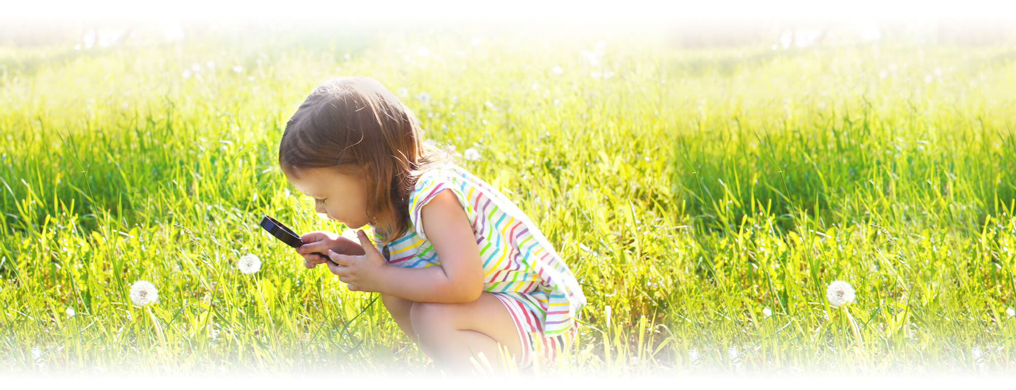 Prek girl in field with magnifying glass