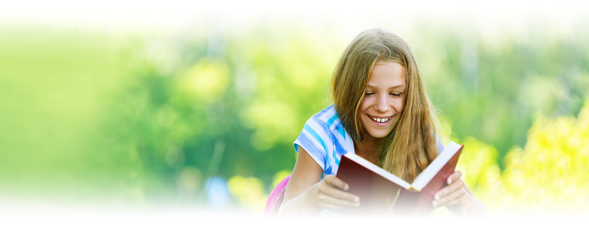 student girl lying on grass reading book