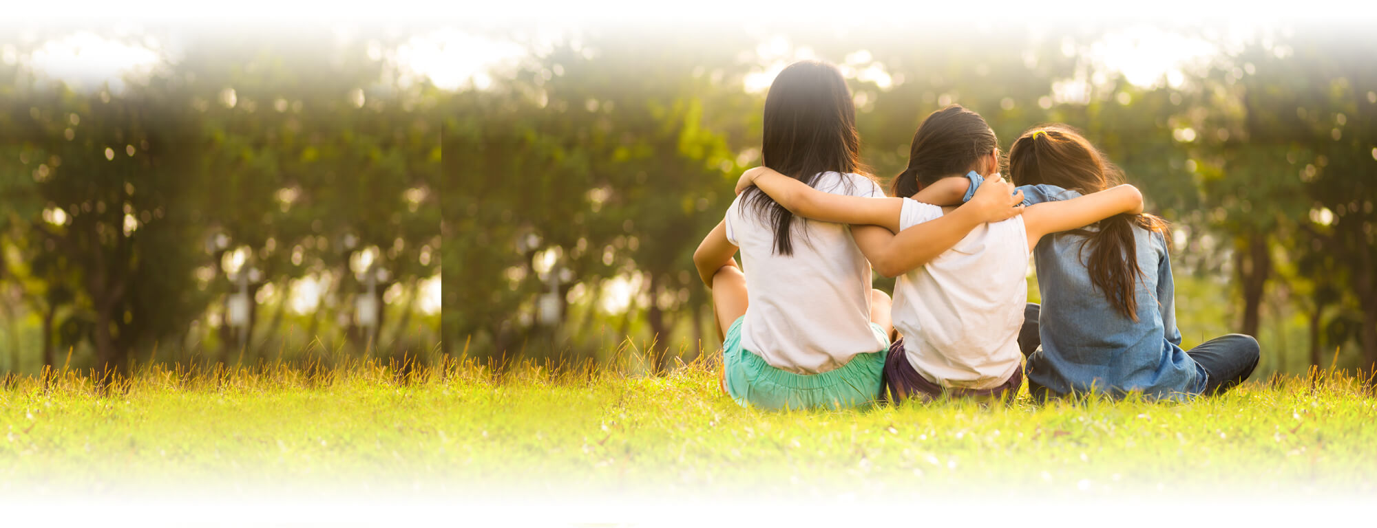 three student girls sitting on grass with arms around each other