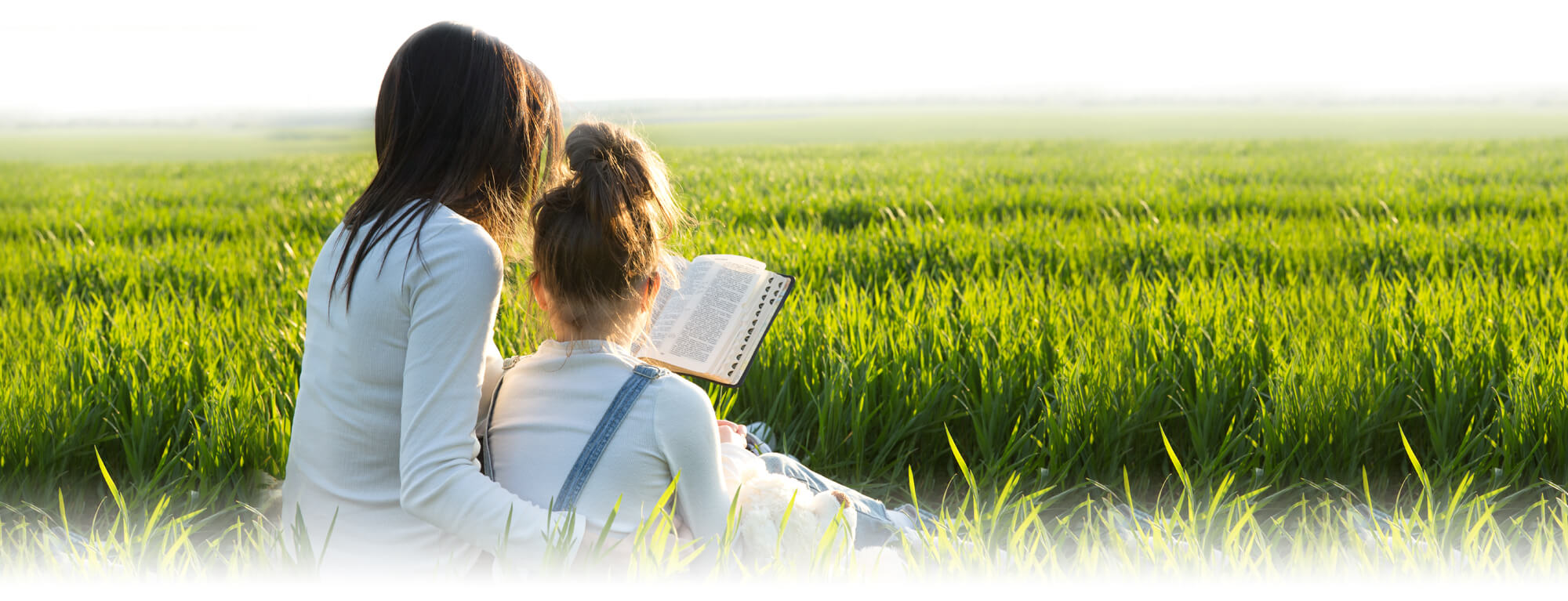 mother and girl reading Bible in a field